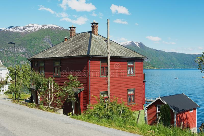 Традиционный красный цвет покрасил норвежский дом с Sognefjord на предпосылке в Balestrand, Норвегии стоковые фотографии rf