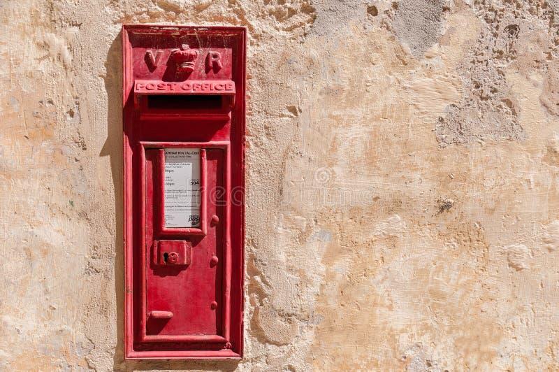 Традиционный красный postbox установил в стену стоковые изображения