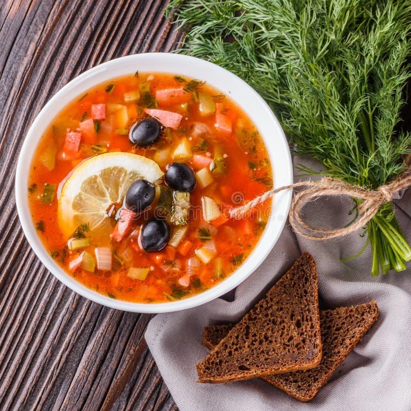 Традиционный российский мясной суп 'Солянка' в чашке на заросшем деревянном столе стоковое изображение