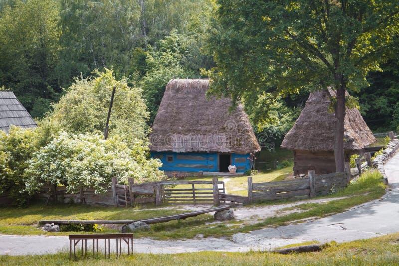 Традиционный украинский старый деревянный дом с соломенной крышей, пастырским весенним днем, небольшим двором и деревянной загоро стоковая фотография rf