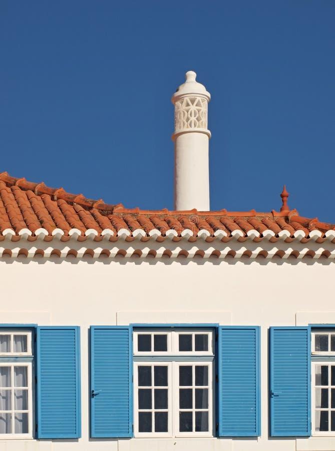 Традиционный фасад дома в голубой белизне с типичным камином стоковое фото
