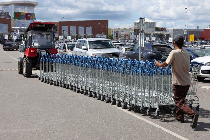 Трактор Беларусь вытягивает строку магазинных тележкеа в МЕГА супермаркете, Москве стоковые изображения rf