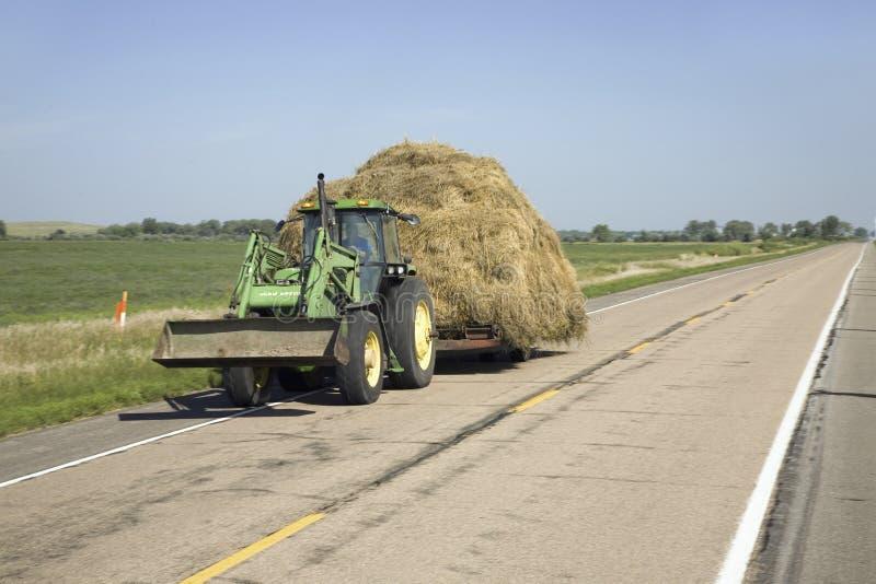 Трактор вытягивая сено вниз Редакционное Фотография