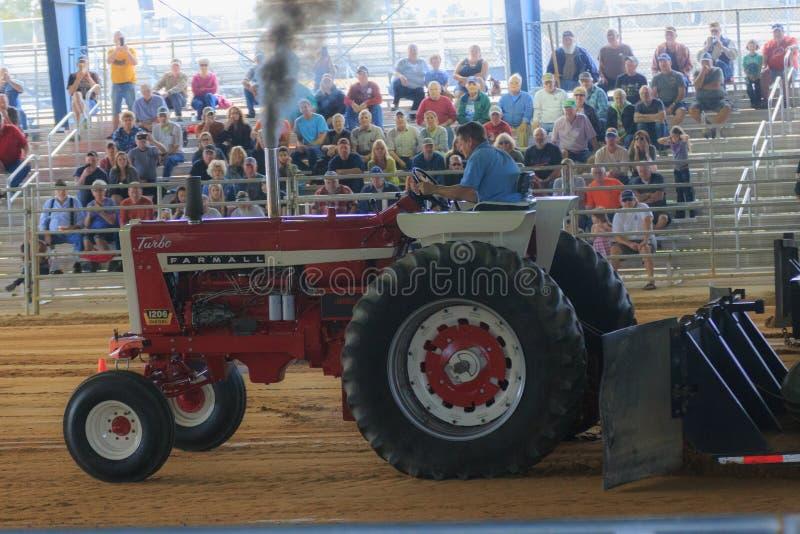 Трактор вытягивая с винтажным трактором Farmall стоковая фотография
