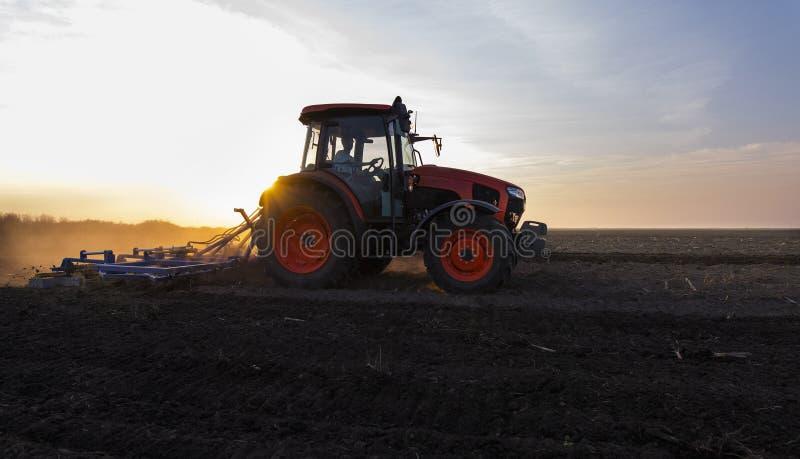 Трактор готовит землю на закате стоковые фото