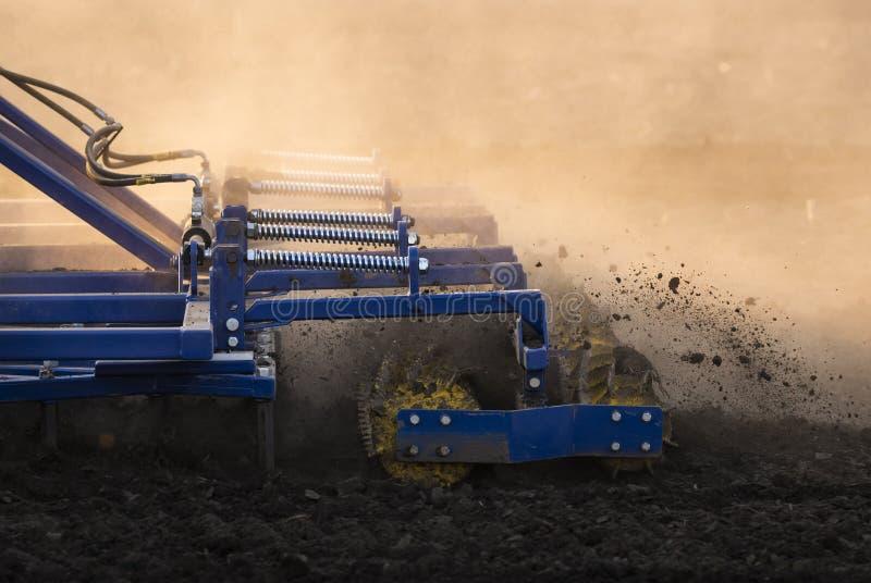 Трактор готовит землю на закате стоковые изображения