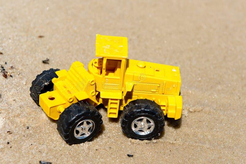 Трактор игрушки в влажном песке прибой лета моря сандалий праздников пляжа Специальная миниатюра стоковая фотография