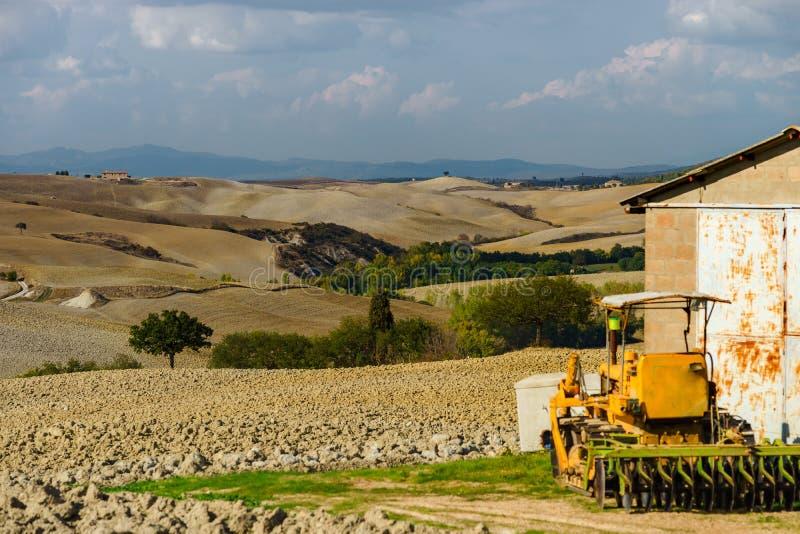 Трактор на поле, Тоскана, осенний вспахивать, аграрная концепция стоковые изображения rf