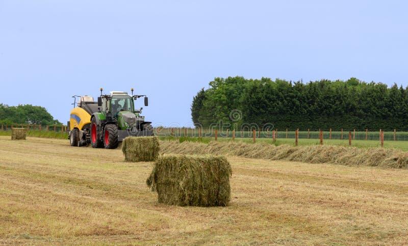 Трактор на соломе фермы тюкуя стоковые фотографии rf