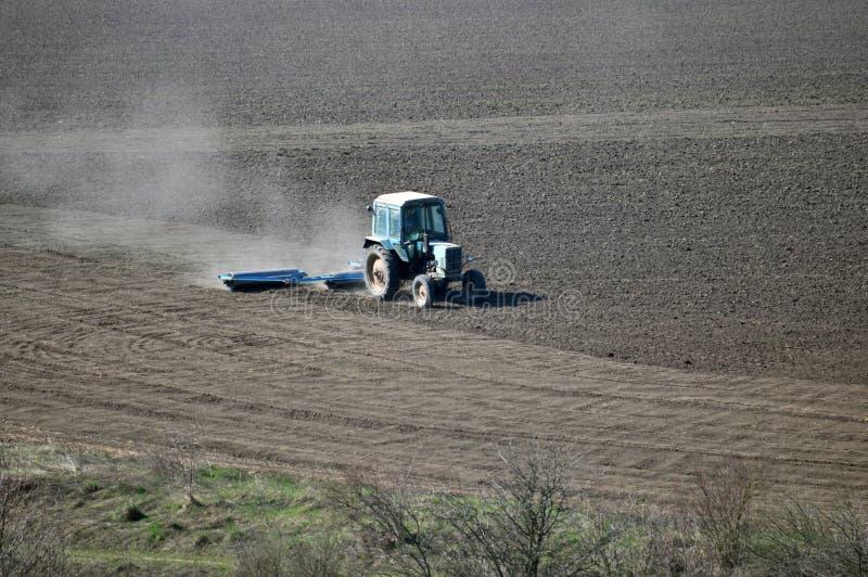 Трактор подготавливает почву для засевать аграрные урожаи стоковое фото rf