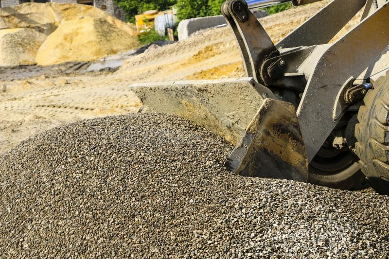 Трактор собирает ветроуловитель с гравием экскаватор извлекает песок и гравий для конкретного смешивания стоковое изображение