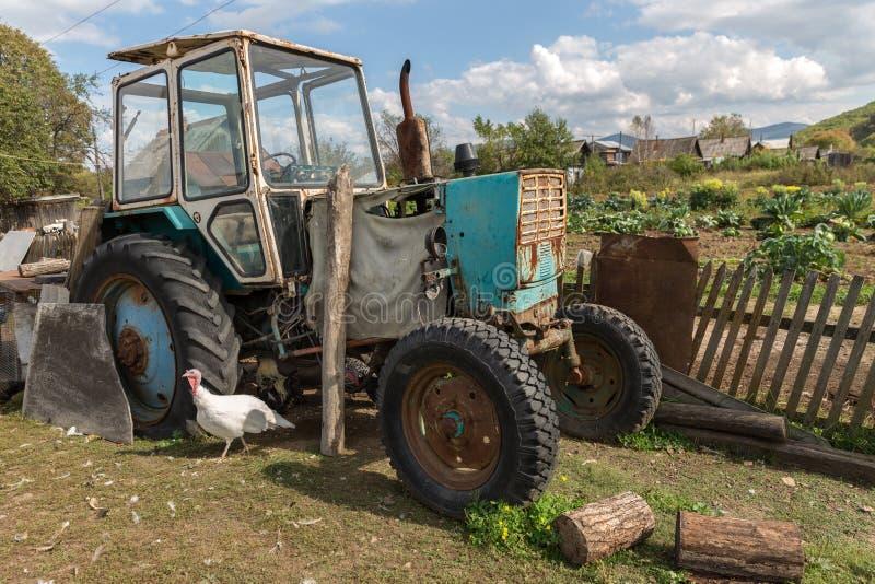 Трактор стоит в деревне стоковая фотография