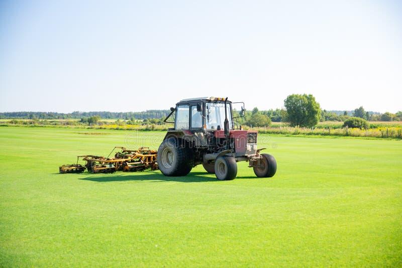 Трактор с соплом для заботы лужайки поля для поло лошади в работе Трава выключения принимает от механически частей никакого стоковое фото
