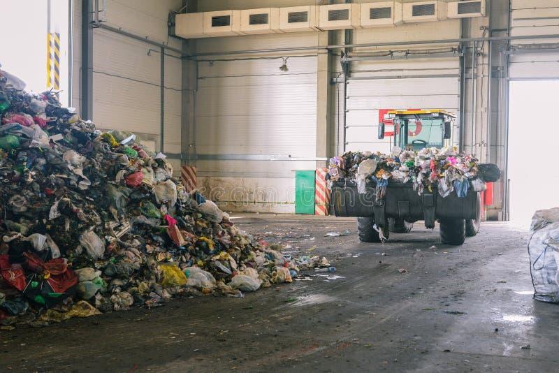 Трактор транспортирует отброс на завод для обработки и сортировать отхода Поднятое ведро бульдозера с отходом Куча погани в стоковые фото