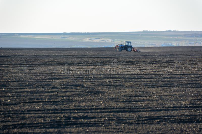 Трактор фермы с плужком в поле на ферме в солнечном дне Фермер в тракторе подготавливая землю Сезон вспахивать стоковое фото rf
