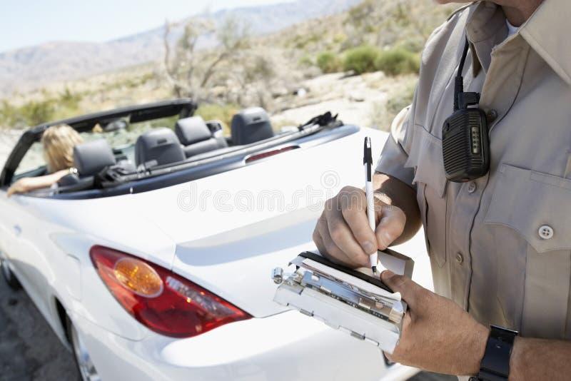Транспортный билет сочинительства полицейского к женщине сидя в автомобиле стоковое фото rf