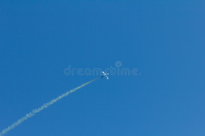 Трассировка конденсации выделила заходящим солнцем за самолетом в голубом небе След конденсации устаревший след заворота стоковые фотографии rf