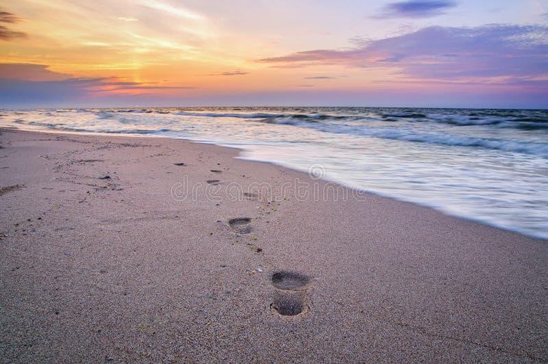 Трассировки персоны на море приставают к берегу, восход солнца стоковая фотография