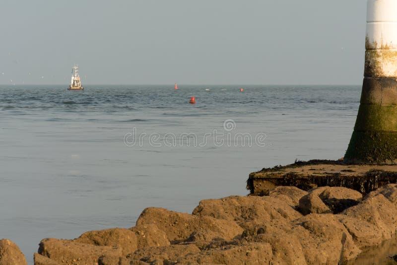 Траулер причаливая малому белому маяку стоковое фото rf