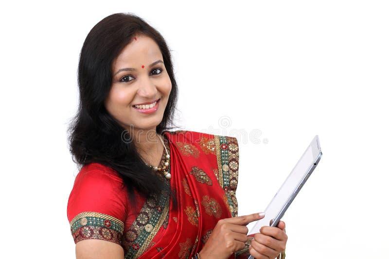 Традиционная индийская женщина держа портативный компьютер стоковое изображение rf