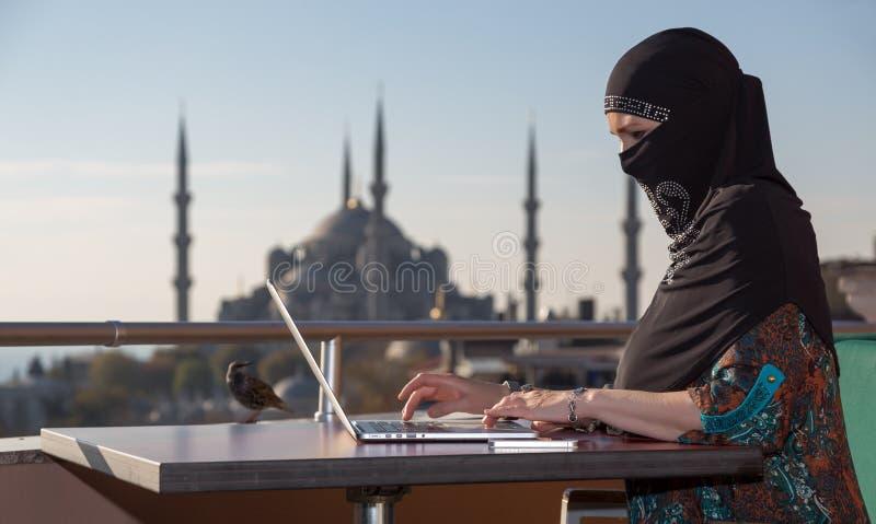 Традиционно одетая мусульманская женщина работая на компьютере стоковое изображение