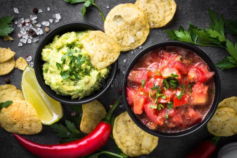 Традиционные латино-американские мексиканские гуакамоле и сальса соуса на b стоковые фото