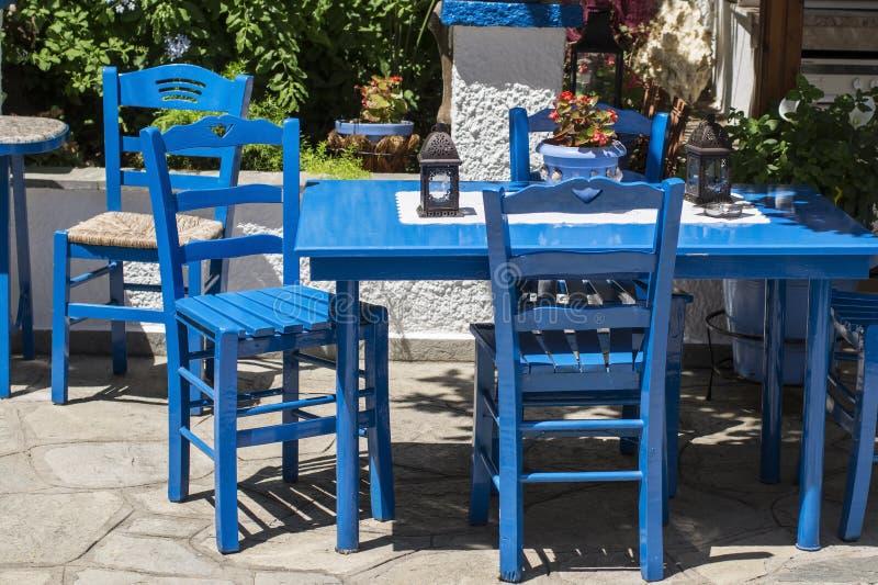 Традиционные голубые греческие стулья в задворк стоковое изображение