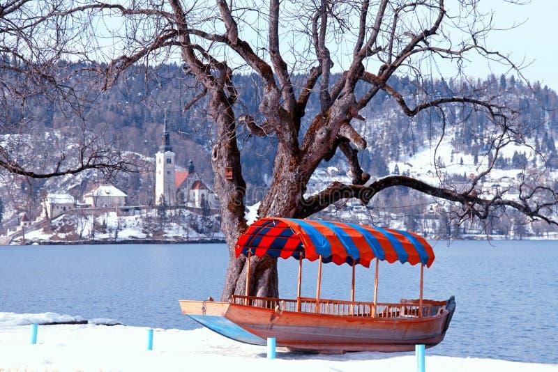 Традиционные словенские шлюпка и церковь на озере кровоточили, Словения стоковая фотография rf