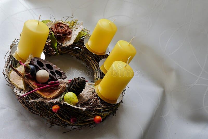 Традиционный домашний сделанный венок пришествия с желтыми свечами и высушенными декоративными элементами стоковое изображение