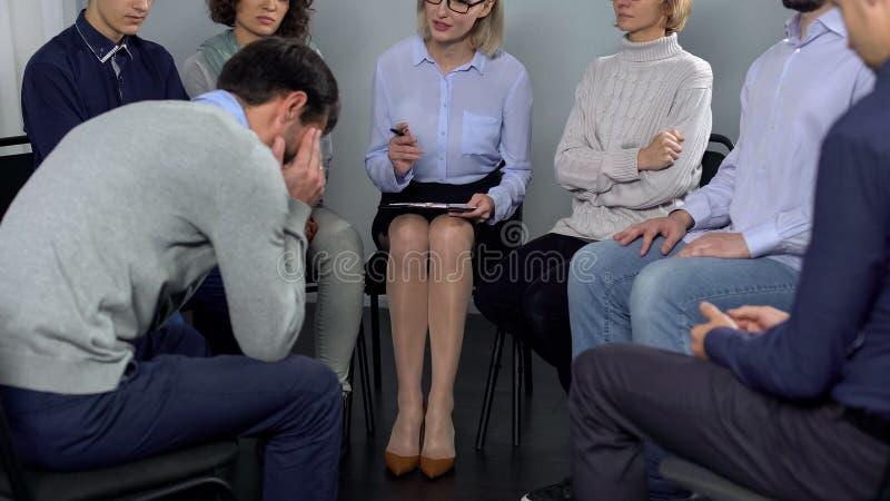 Тревоженый молодой человек говоря о его проблеме к психологу на терапии группы стоковые изображения rf
