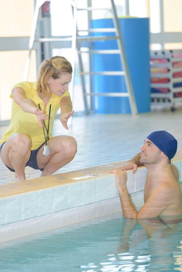 Тренер заплывания советуя пловцу в бассейне стоковая фотография