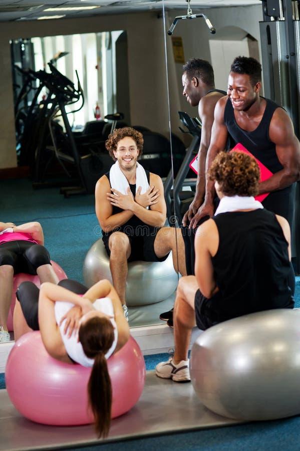 Тренер инструктируя клиентов гимнастики стоковое изображение
