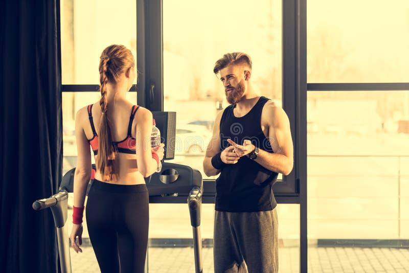 Тренер инструктируя тренирующую стоя на третбане в спортзале стоковое изображение rf