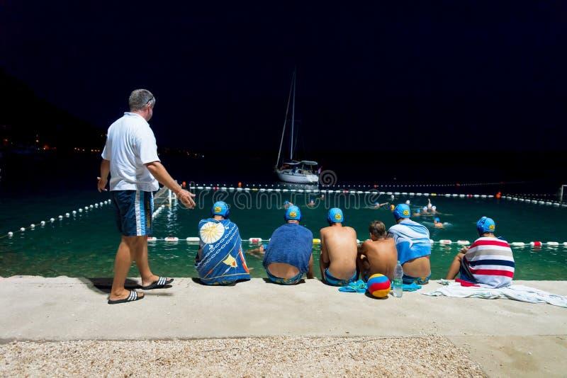 Тренер и игроки водного поло наблюдая спичку в Omis стоковые фотографии rf