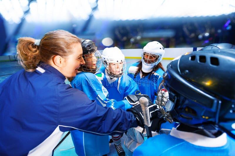 Тренер и хоккеисты кладя руки в груду стоковая фотография rf