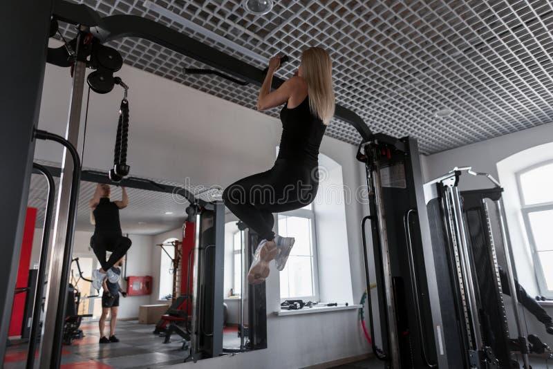 Тренер молодой женщины в sportswear с тонким телом делая тренировки для рук внутри помещения Девушка выполняет физический exertio стоковые фотографии rf