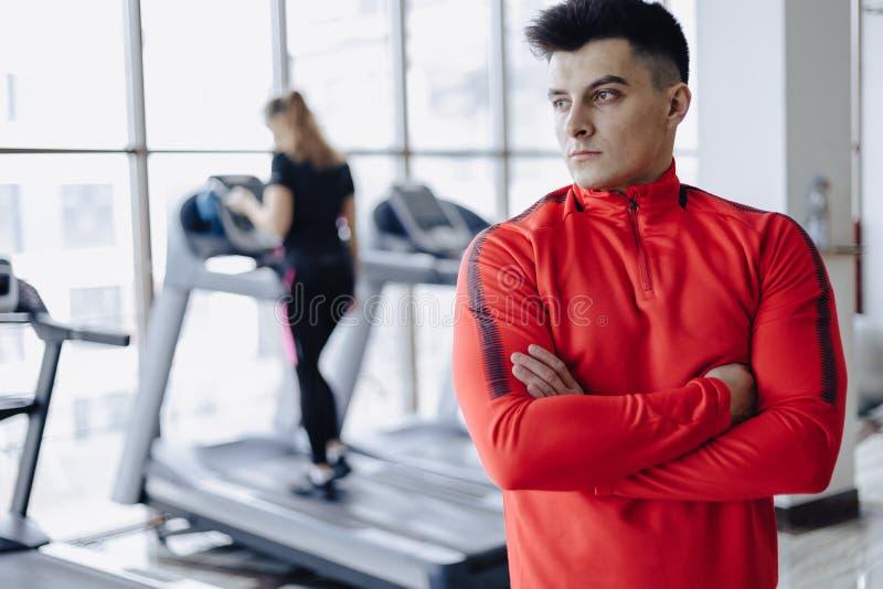 Тренер парня в спортзале на предпосылке людей на третбанах стоковое изображение