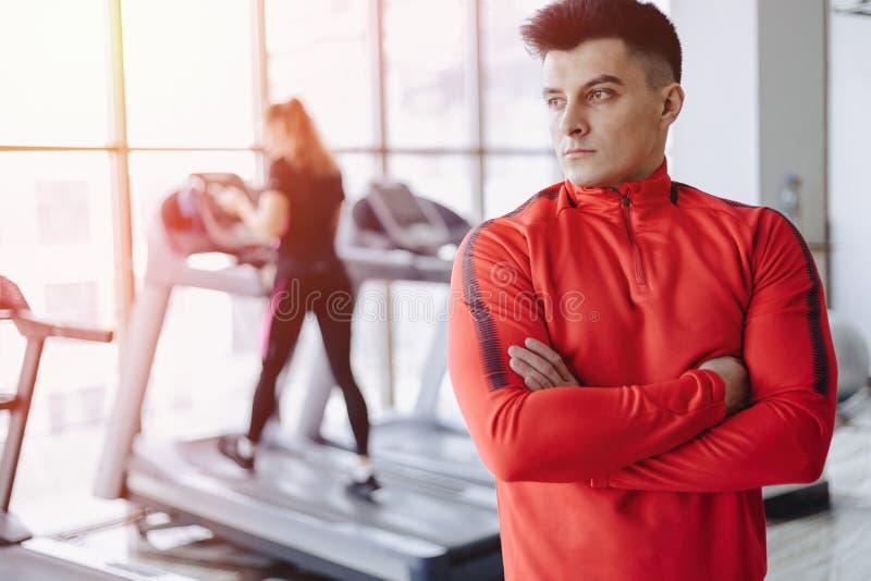 Тренер парня в спортзале на предпосылке людей на третбанах стоковое фото rf
