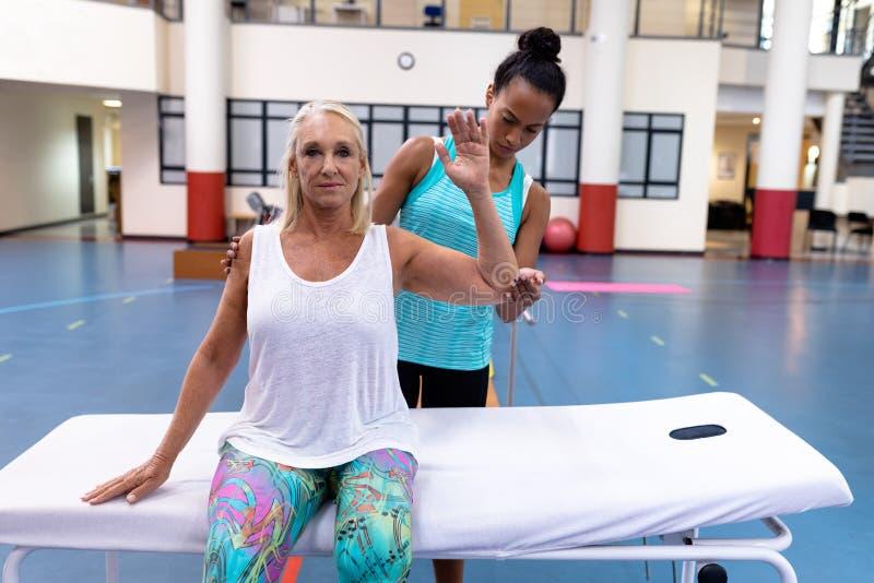 Тренер помогая неработающей активной старшей женщине для того чтобы работать в спортивном центре стоковое изображение rf