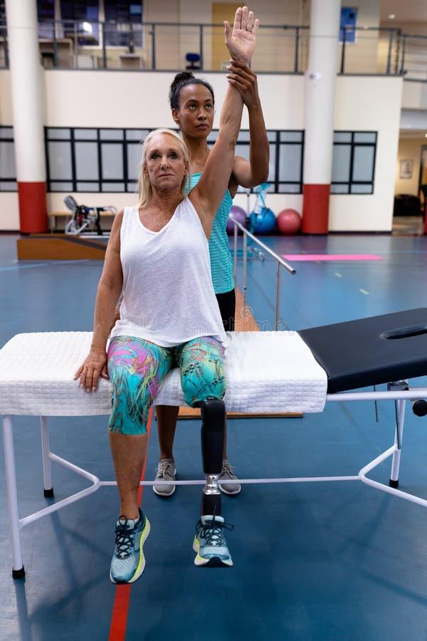 Тренер помогая неработающей активной старшей женщине для того чтобы работать в спортивном центре стоковые изображения