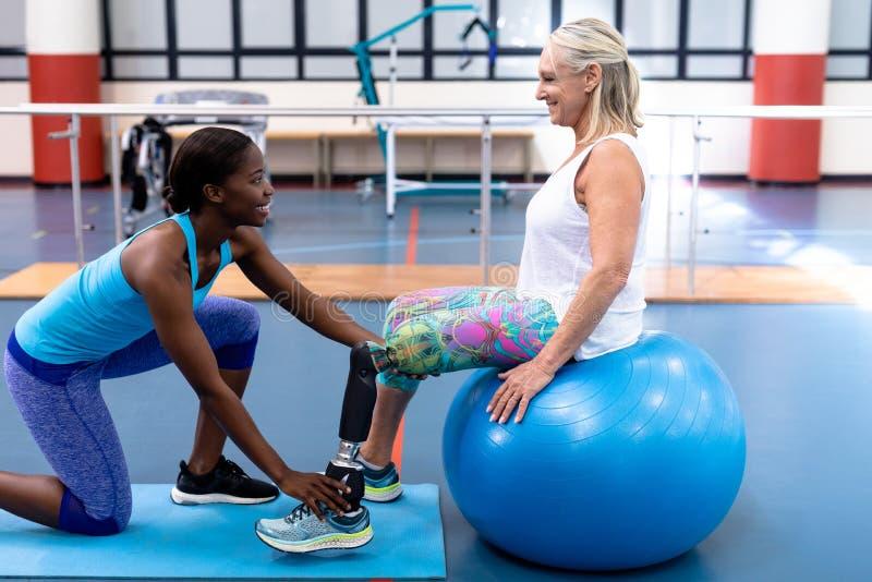 Тренер помогая неработающей старшей женщине в спортивном центре стоковые фотографии rf