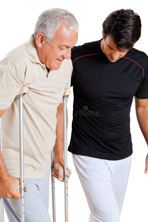 Тренер помогая старшему человеку с костылями стоковая фотография