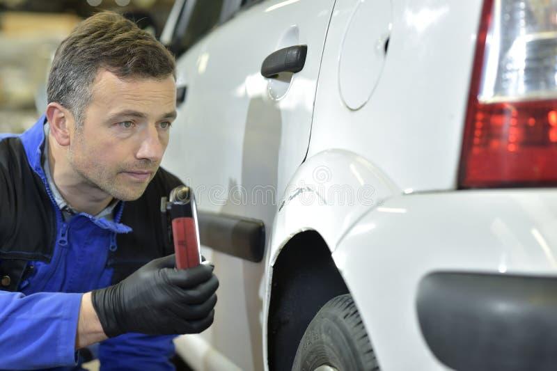 Тренер-построитель проверяя репарации автомобиля для того чтобы сделать стоковая фотография rf
