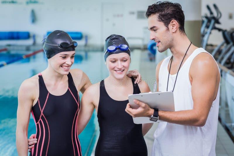 Тренер разговаривая с усмехаясь пловцами стоковые фотографии rf