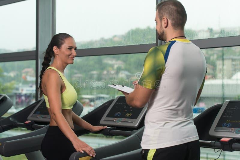 Тренер с доской сзажимом для бумаги контролирует женщину пока она бежать стоковые фото