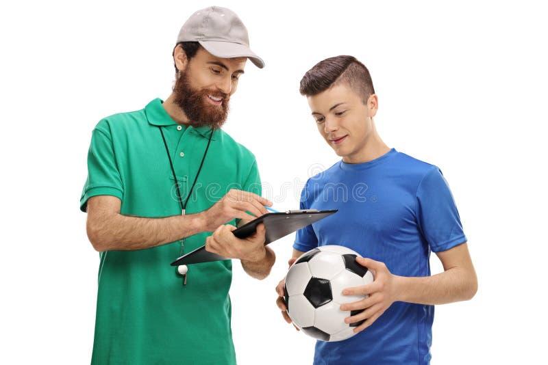 Тренер футбола советуя подростковому игроку стоковое изображение