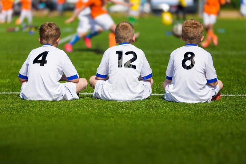 Тренировать футбол молодости Молодые мальчики сидя на футбольном поле стоковые фотографии rf