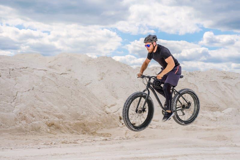 Тренировка велосипедиста в меловом карьере Зверский человек на тучном велосипеде стоковое изображение