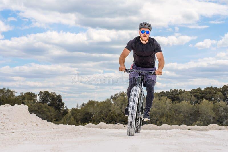 Тренировка велосипедиста в меловом карьере Зверский человек на тучном велосипеде стоковые фотографии rf