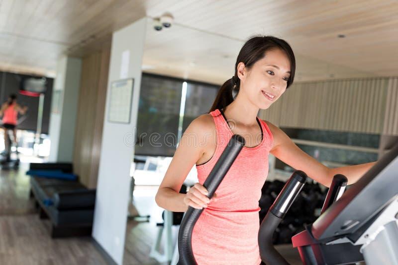 Тренировка женщины на эллиптической машине в спортзале стоковые фотографии rf